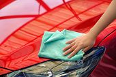 hand women hold water over the red car for washing with microfiber cloth poster