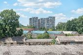 Roofs of refugee center cheep old prefabricated barracks for emigrants or migrants in the city with normal residential buildings in the backgrounds poster