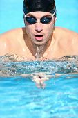 Swimmer - man swimming breaststroke. Male sport fitness model doing breast swimming in pool wearing swimming goggles and swim cap. poster