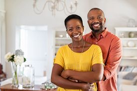 Smiling mature couple holding each other at home. Loving african couple standing in living room embracing and looking at camera. Husband hugging wife from stomach at new apartment with copy space.