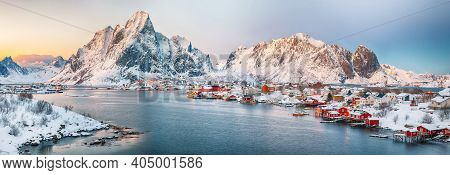 Fantastic Evening Panorama Of Reine Town. Red Rorbuers On The Shore Of Reinefjorden. Popular Travel