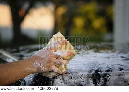 Washing The Car Roof With A Microfiber Cloth. Car Wash. Water, Foam, Shampoo. Car Roof And Hand With