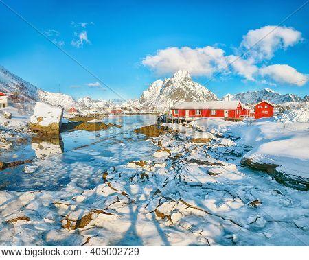Breathtaking Winter Sunny View On Reine Village And Gravdalbukta Bay With Cracked Ice. Snowy Mountai