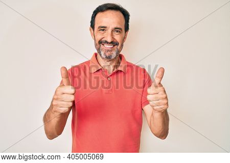 Middle age hispanic man wearing casual clothes success sign doing positive gesture with hand, thumbs up smiling and happy. cheerful expression and winner gesture.