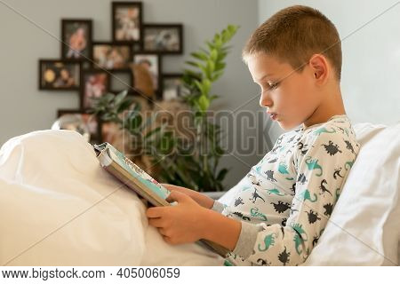 The Boy Reads A Book At Home. Before Going To Bed, The Student Lies In Bed And Studies The Encyclope