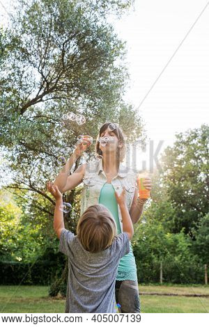 Young Mother Blowing Soap Bubbles For Her Toddler Child Playing Outside On A Beautiful Sunny Day.