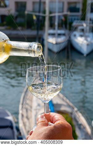 Pouring Of Cold White Wine In Glass In Summer With Sail Boats Haven Of Port Grimaud On Background, P
