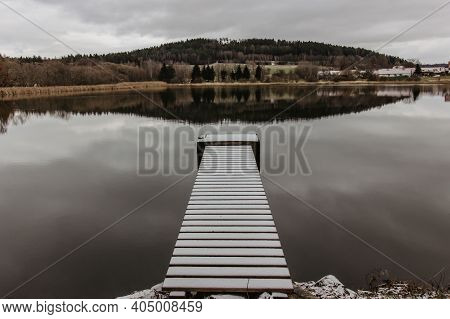 Wooden Pier On The Lake. Winter Lake With Pier And Snow. Cloudy Sky, Lake With Hills In Background.