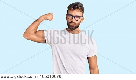 Young hispanic man wearing casual clothes and glasses strong person showing arm muscle, confident and proud of power