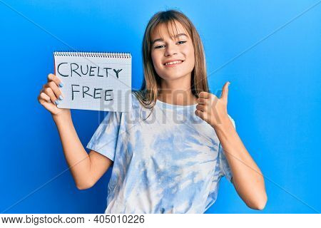 Teenager caucasian girl holding cruelty free cosmetics banner smiling happy and positive, thumb up doing excellent and approval sign