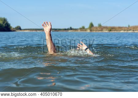 Hands Of A Drowning Man Above Water In Need Of Help.