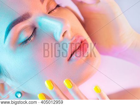 High Fashion model girl in colorful bright UV lights posing in studio, portrait of beautiful woman with trendy make-up and manicure. Art design, colorful make up. Over colourful background