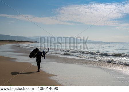 Barbate, Spain - 19 January, 2021: Surfer Walking Along A Beach With A Hydrofoil Surfboard