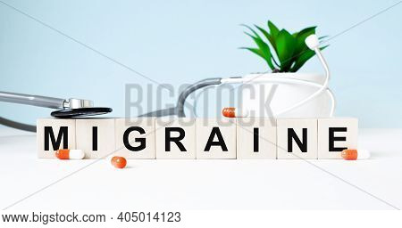 The Word Migraine Is Written On Wooden Cubes Near A Stethoscope On A Wooden Background. Medical Conc