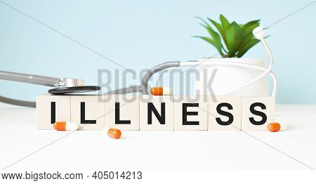The Word Illness Is Written On Wooden Cubes Near A Stethoscope On A Wooden Background. Medical Conce