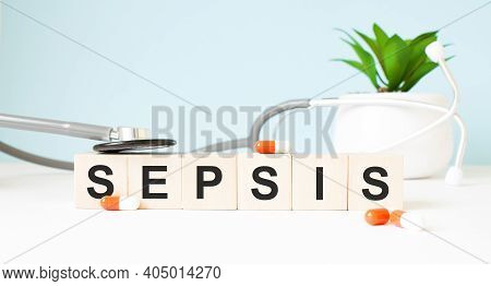 The Word Sepsis Is Written On Wooden Cubes Near A Stethoscope On A Wooden Background. Medical Concep