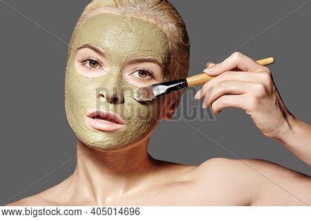 Beautiful Woman Applying Green Facial Mask. Beauty Treatments. Spa Girl Apply Clay Facial Mask On Gr