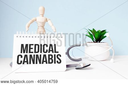The Text Medical Cannabis Is Written On Notepad And Wood Man Toy Near A Stethoscope On A Blue Backgr