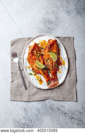 Baked Red Perch Seabass With Red Sauce And Lemon On White Plate. Top View