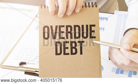 Text Overdue Debt On Brown Paper Notepad In Businessman Hands On The Table With Diagram. Business Co