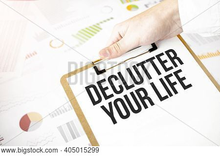 Text Declutter Your Life On White Paper Plate In Businessman Hands With Financial Diagram. Business