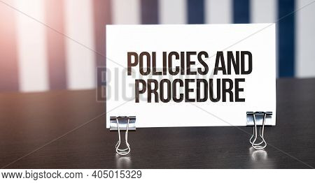 Policies And Procedure Sign On Paper On Dark Desk In Sunlight. Blue And White Background