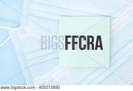 Piece Of Paper With Phrase Ffcra On Pile Of Blue Medical Masks. Coronavirus Pandemic Concept