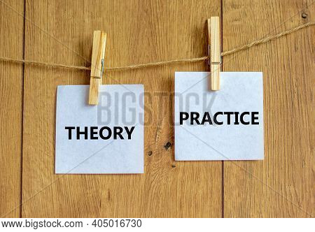 Theory And Practice Symbol. Wooden Clothespins With White Sheets Of Paper. Words 'theory Practice'.