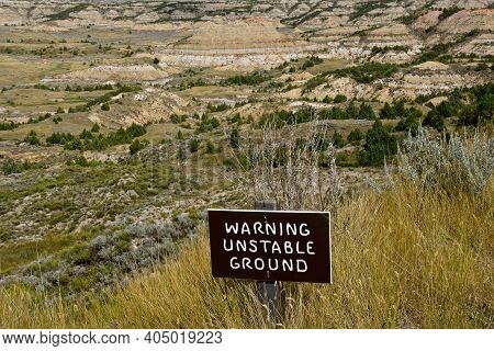 A Sign Warning Hikers Of Unstable Ground At The Entrance Of Theodore Roosevelt National Park Badland