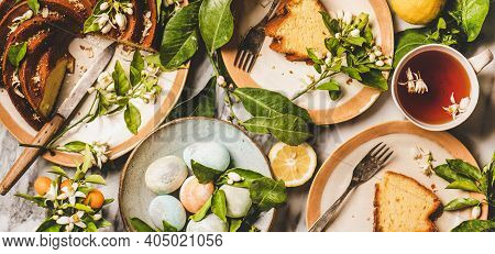 Easter Holiday Dinner Table Setting. Flat-lay Of Colorful Easter Eggs, Lemon Cake With Citrus Tree B