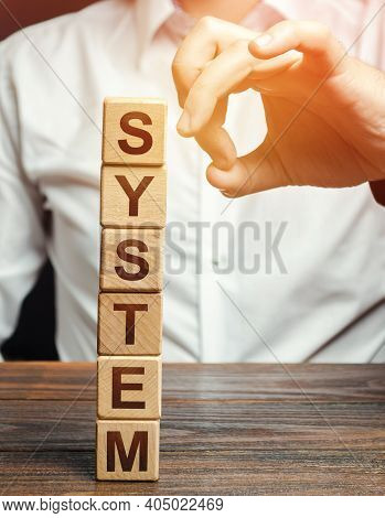 Men Knocks Down Wooden Block Tower With Word System. System Destruction Concept. The Threat Of Viola