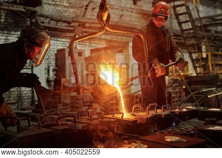 The welder works in the factory shop two steel workers melting metal