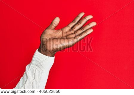 Arm and hand of african american black young man over red isolated background presenting with open palm, reaching for support and help, assistance gesture