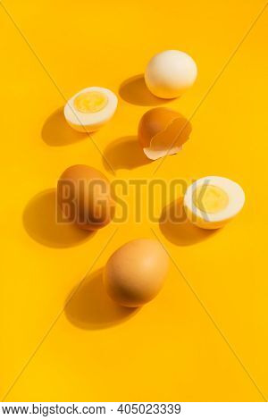 Brown Chicken Raw And Hard Boiled Fresh Eggs On Yellow Background. Healthy Food Or Happy Easter Conc