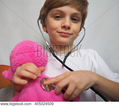 Little Boy With Blond Hair Playing With Stethoscope At Doctor's Office. Pink Plush Toy In The Hands