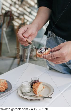 Hand Spreads English Scones With Cream Cheese And Strawberry Jam, A Scone Is A Single-serving Quick