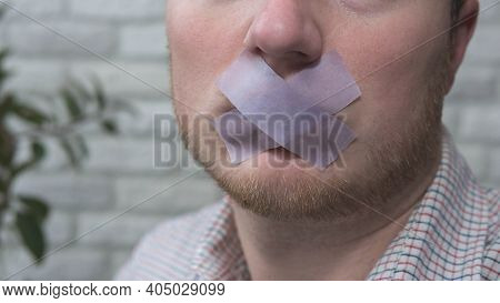 A Man With A Tape Taped Over His Mouth, A Close-up Of His Face, A Man With A Tape Over His Lips