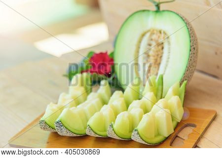 Closeup To Fresh Green Melon On Wood Plate