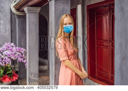 Woman Tourist Wearing A Medical Mask During Covid-19 Coronavirus On Background Of Temple Ngoc Son In
