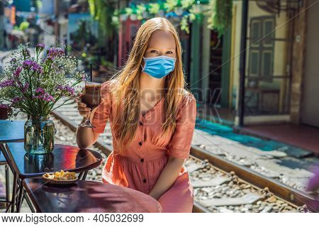Young Woman Traveler Wearing A Medical Mask During Covid-19 Coronavirus Drinks Coffee Sitting By The