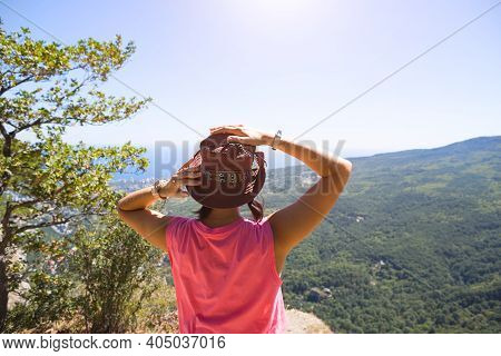 A Woman In A Hat Looks At The Panoramic View From The Mountain To The Sea And The Forest. Tourist, T