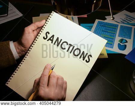 Hands Hold A List Of Economic Sanctions.