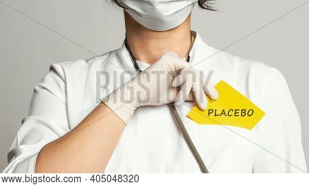 Cropped View Of Doctor In A White Coat And Sterile Gloves Holding A Note With Word - Placebo. Medica