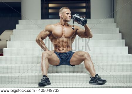 Fitness Man In Gym Drinking Water After Workout. Fitness And Bodybuilding Healthy Background. Caucas