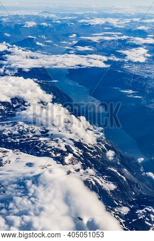 View From Airplane To Clouds And Norwegian Fjords Landscape. Aircraft Flying Over Norway Scandinavia