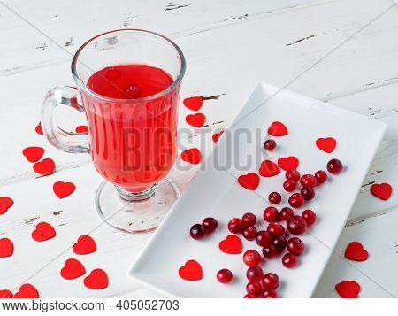 Fresh Cranberry Drink In A Glass Cup On A Wooden White Background. Many Small Red Hearts As A Symbol