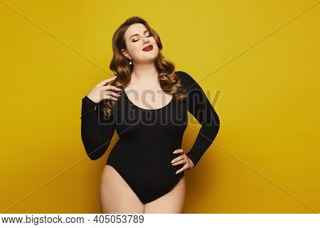 Plus-size Model Girl With Bright Makeup In Black Bodysuit Posing At The Yellow Background. Young Plu