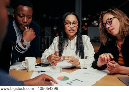 Young Group Of Multi Ethnic Business Team Analyzing Financial Documents With Each Other At Night Bef