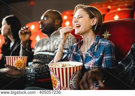 Friends Watching A Movie In The Cinema With Popcorn. People Sit In The Armchairs Of The Cinema And L