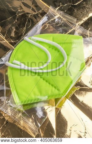 New Green Respirator Ffp2, Kn95 In A Plastic Bag On Shiny Crumpled Packing Paper. Medical Respirator